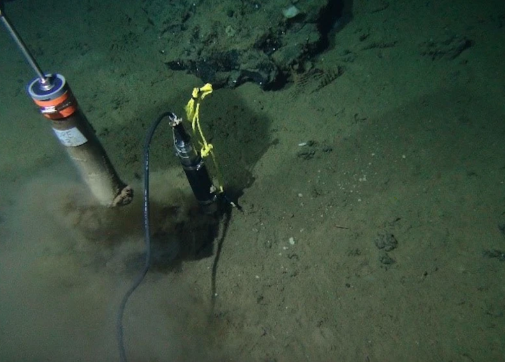 A murky green-brown ocean floor with a tool drilling into the seafloor