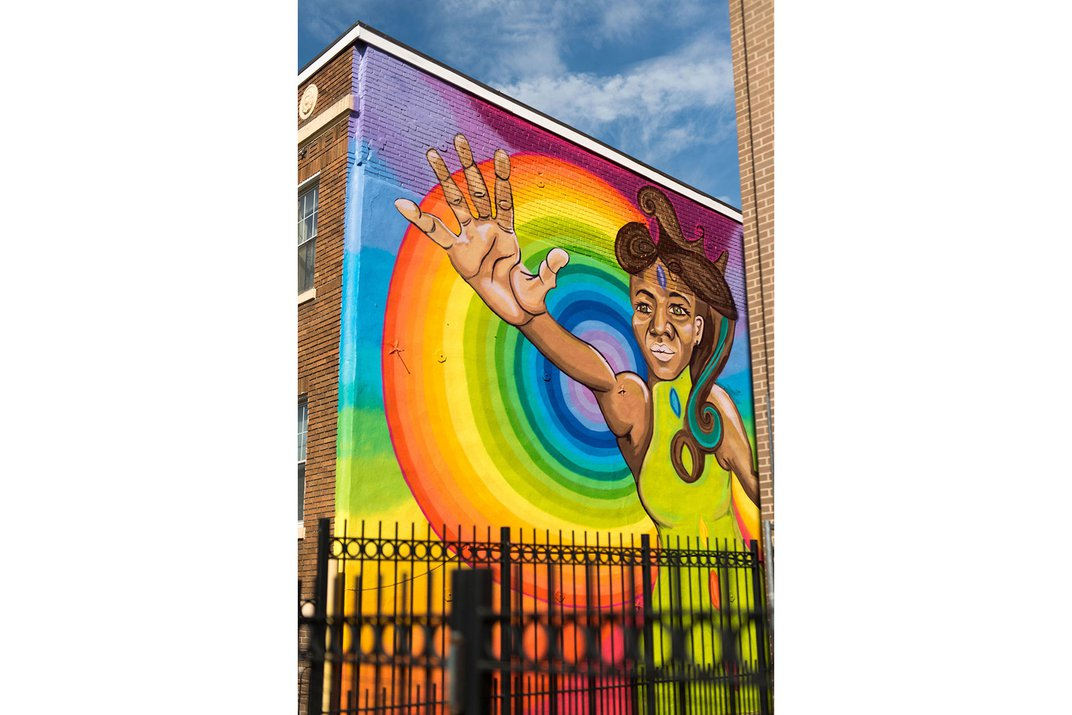 Mural on the side of a brick rowhouse, showing a Black woman reaching out with an open hand, and rainbow pattern behind her.