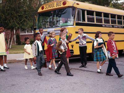 Children cross the street in front of a yellow school bus in 1965.