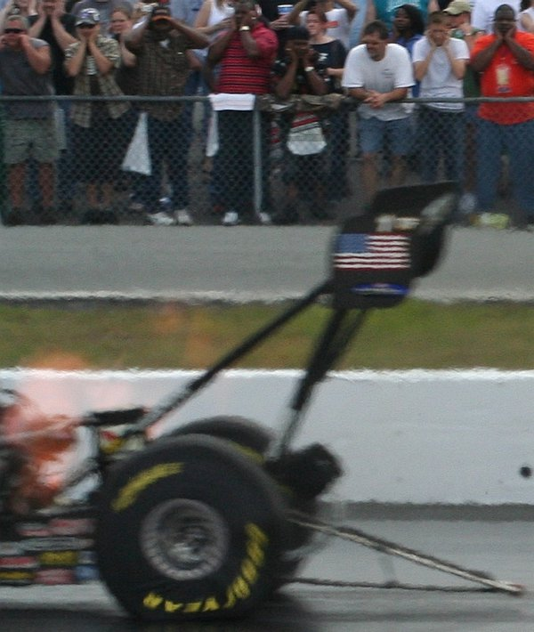 A Top Fuel Dragster roars by as spectators hold their ears. thumbnail