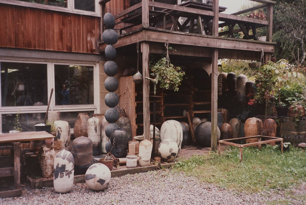 Collection of large pottery vessels, mostly in browns and earth tones, outsdie of a wooden house.