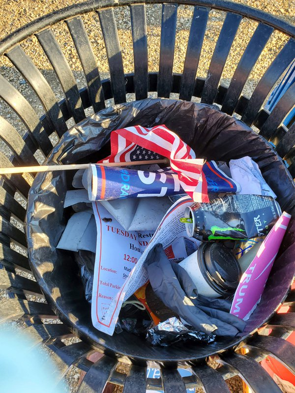A trash can filled with signs and other ephemera