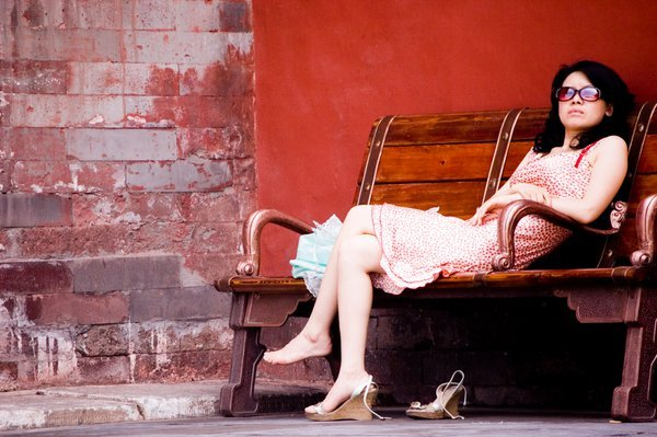 A fashionable lady rests from the sun's heat in the forbidden city. thumbnail