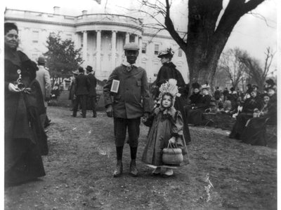 This 1898 photograph shows a young black boy holding hands with a young white girl during the Easter egg roll. The contraption on her head is an Easter bonnet.