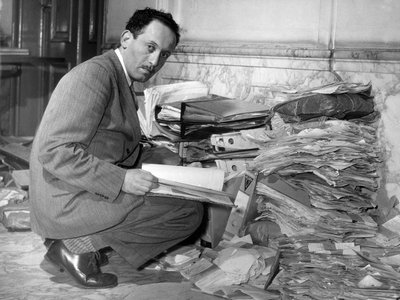 Louis de Jong, founder of Dutch Institute for War Documentation, examining documents on the Holocaust.