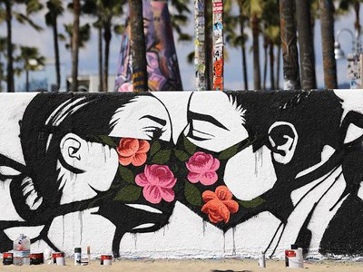 A street art piece by artist Pony Wave depicts two people kissing while wearing face masks on Venice Beach in Venice, California.