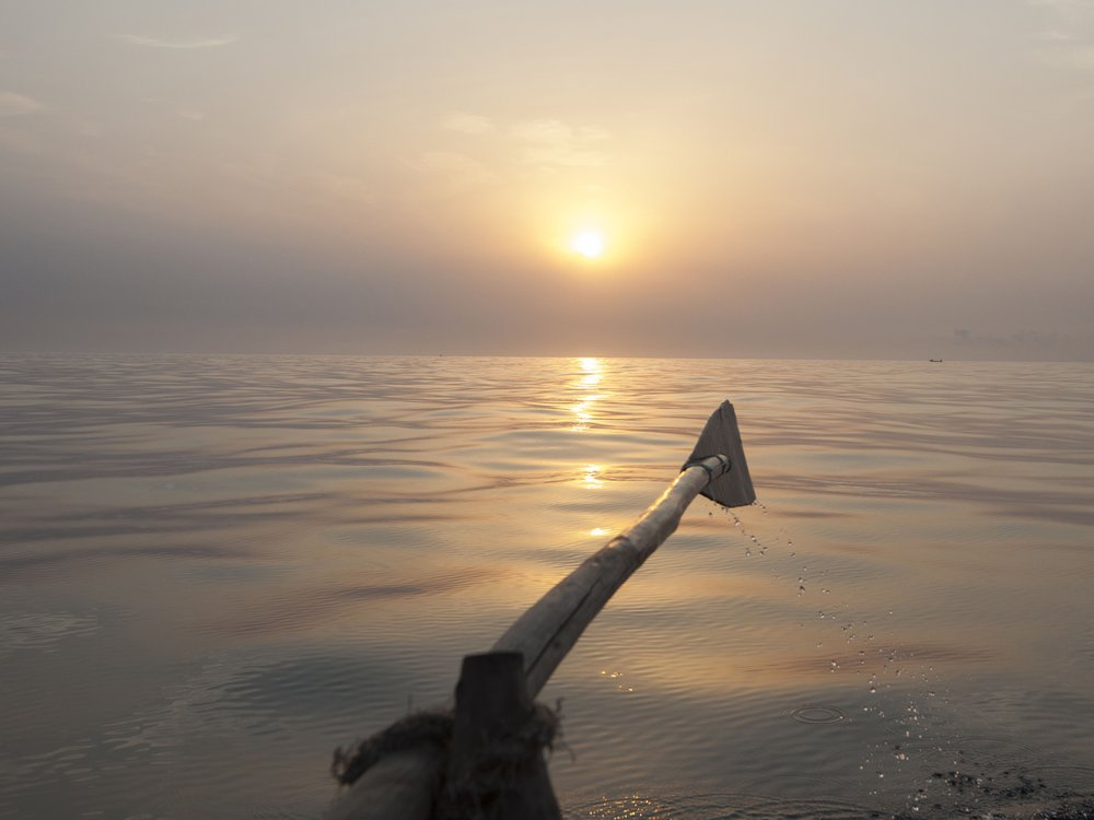 A view of an oar raised parallel to the water as the sun slowly sets