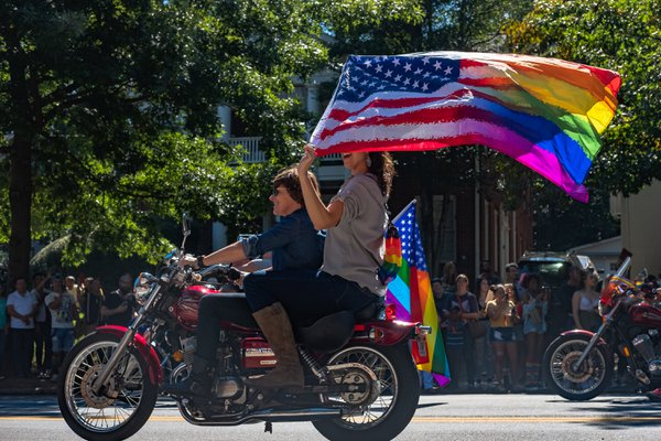 Celebrating pride on a motorcycle with a rainbow flag. thumbnail