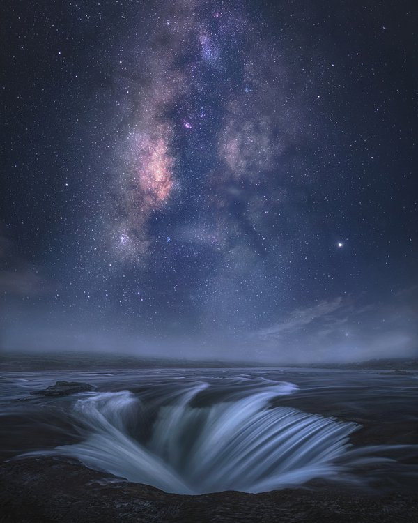 "This image was created close to the town of Amlarem (Meghalaya, India) in September 2019. My vision was to capture the flow of water along with a perfectly aligned Milky Way core, but for that, it took me seven visits to the same location in a single year. Sometimes the sky was clear and the Milky Way was aligned but the flow of water wasn't there. At other times the flow of water was there and the sky was overcast, which is a common occurrence when it comes to Meghalaya, which literally translates to ""Abode of Clouds"". For the foreground, a three-shot panorama was created during the blue hour sometime after sunset. For the sky, it is a vertical panorama of 2 shots captured a couple of hours later when the Milky Way was properly aligned with the water flow."