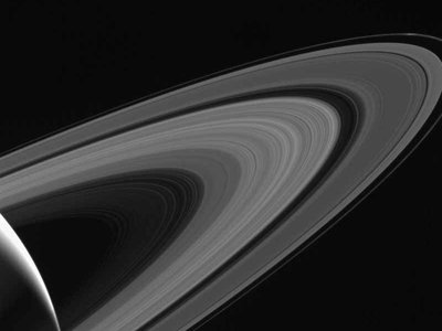 Behind Saturn's icy rings is the moon Tethys, illuminated by the planet's reflected sunlight.