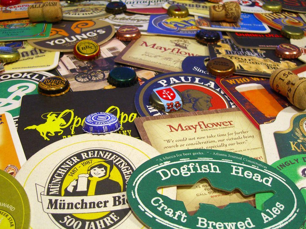 A pile of various beer coasters, wine bottle borks and metal beer bottle caps