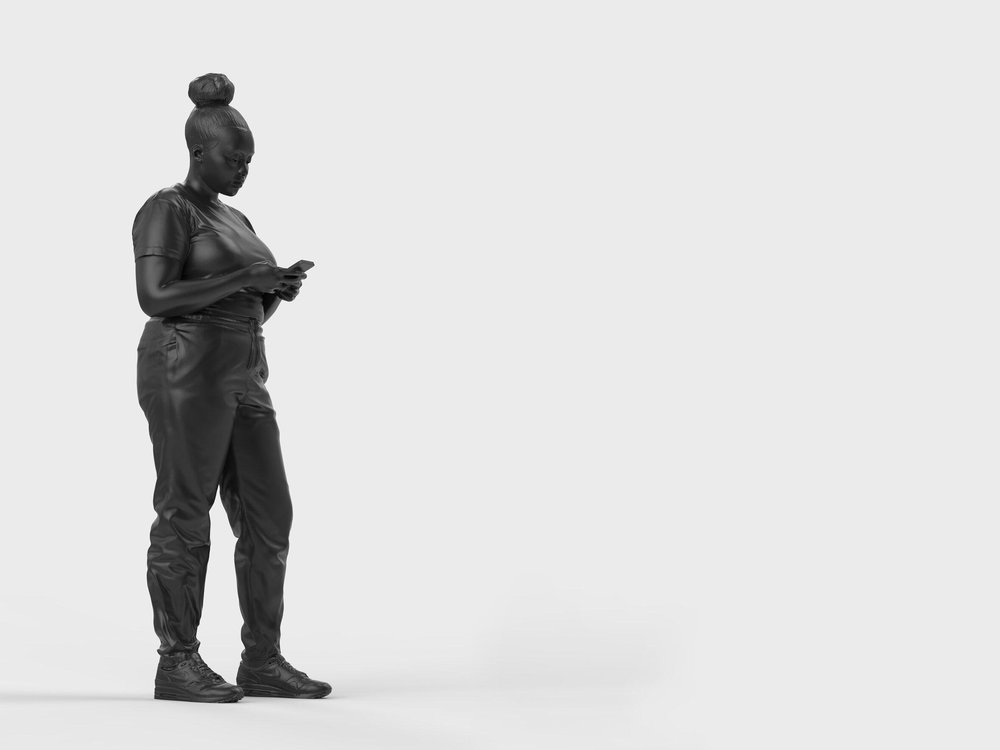 A bronze statue of a black woman surrounded by a plain white background. The woman is standing casually and looking down at her mobile phone, which she holds with both hands.