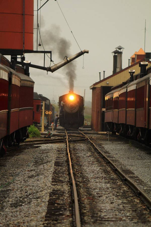 A steam locomotive pulling into a railyard thumbnail