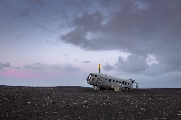 Alone on the secluded plane wreck on the Icelandic black sand beach. thumbnail