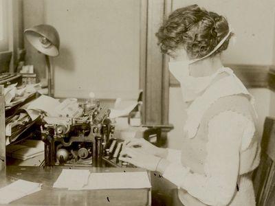 A typist wearing her influenza mask in 1918 New York.
