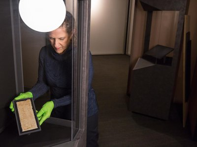 Jane Klinger, chief conservator for the United States Holocaust Memorial Museum, holds one of the cloths that Mansour Omari smuggled out of Syria.
