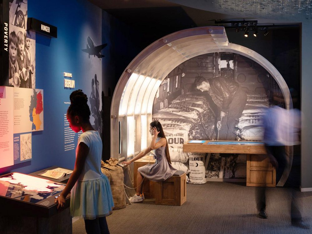 Two young people sit and stand in front of exhibits, reading the text; the blue walls are richly decorated with photographs, maps and information about post-war Europe