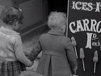 """During World War II, when sugar was rationed to 8 ounces per adult per week, some vegetable alternatives were introduced. These girls don't seem too happy about the """"carrot-on-a-stick"""" option."""