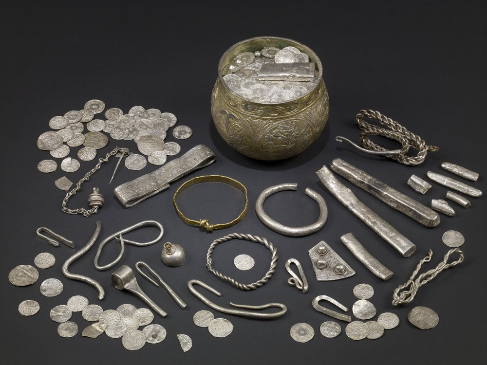 A display of silver Viking artifacts laid out on a table, including a wide mug-like cup, many coins, silver bars and what appear to be bracelets and other jewelry scattered around