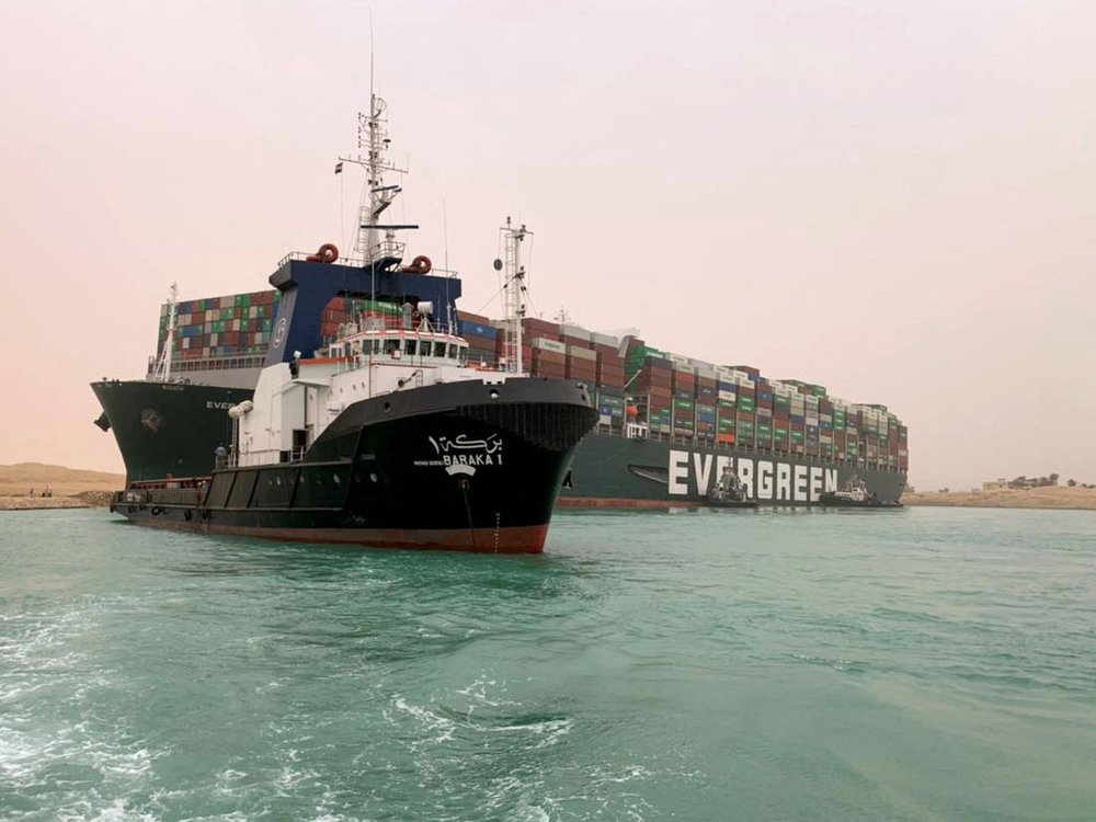 Pictures, is the shipping vessel, the Ever Given stuck on the Suez Canal. There is a tugboat pictured in front trying to pull it free