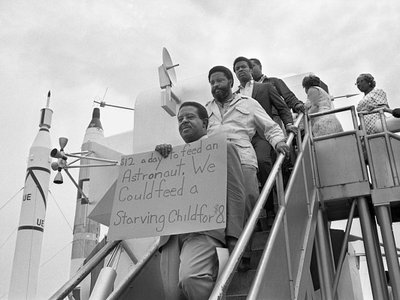 Reverend Ralph Abernathy, Hosea Williams, and other members of the SCLC Poor People's Campaign march through the lunar lander exhibit at Kennedy Space Center before the launch of Apollo 11.