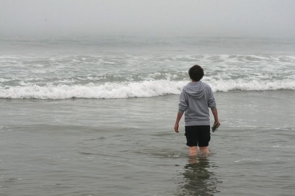 A woman on the beach gazing out into the Pacific Ocean in Santa Monica, California. thumbnail