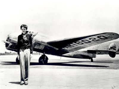 Ameila Earhart standing in front of the Lockheed Electra in which she disappeared in 1937.