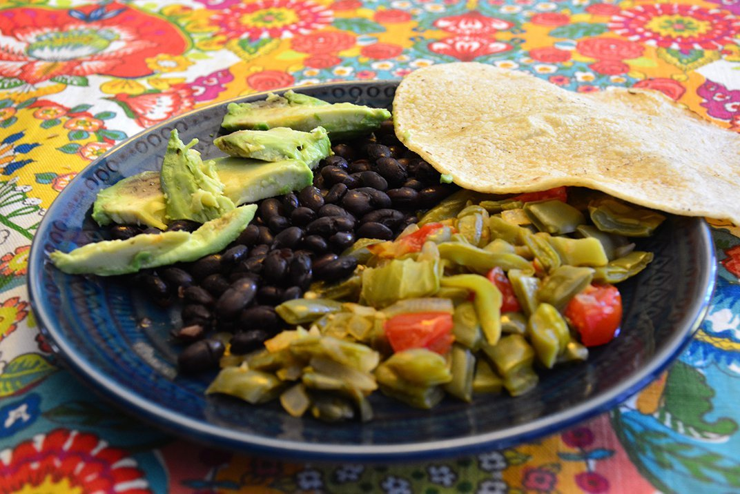 A freshly cooked plate of beans, avocado, sautéed vegetables, and a corn tortilla is placed on a bright, floral table cloth.