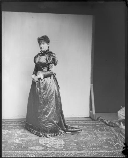 Black and white photograph of woman in long gown with photography backdrop in background.