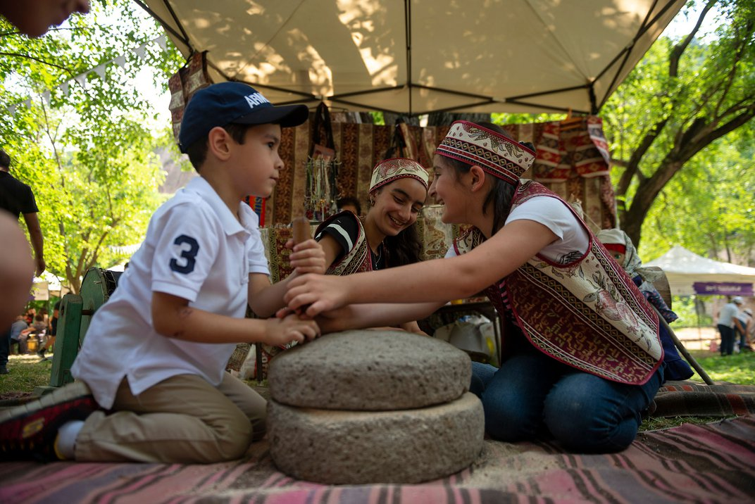 Two girls in Armenian dress and a young boy wearing a baseball cap sit together on the ground, smiling. They are seated around two stones placed on a rug, outdoors.
