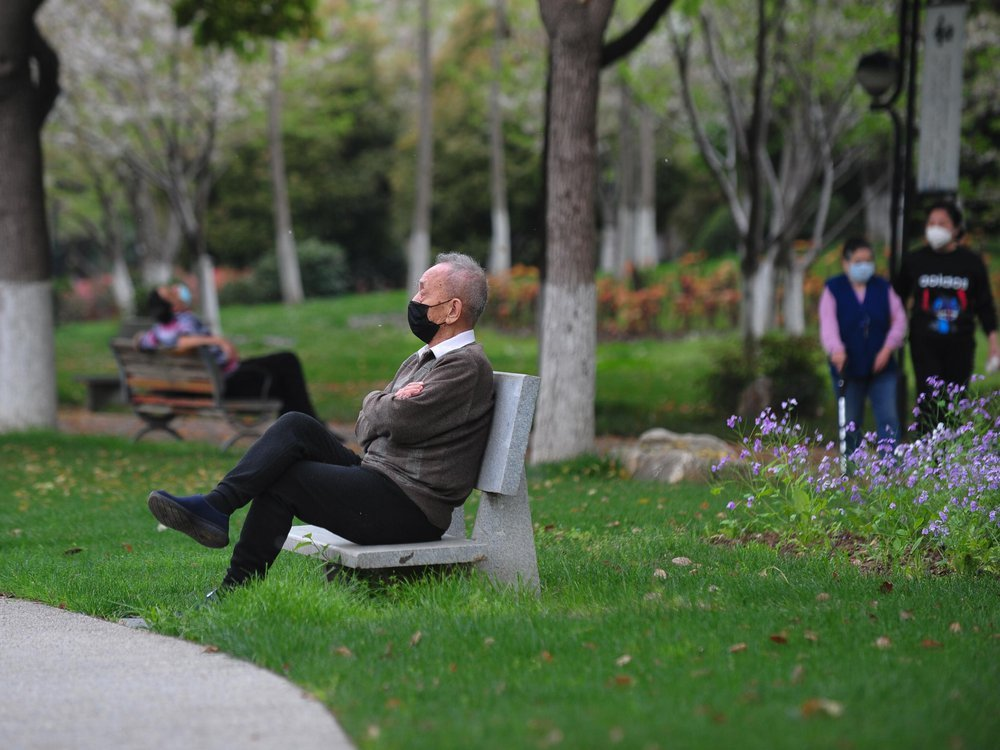 Elderly man rest on a bench after parks reopen in Wuhan on Thursday
