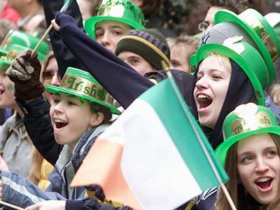 Group of people cheering and waving Irish flags during the St. Patrick's Day parade in New York City.