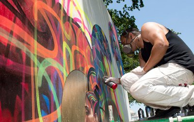 """An artist works on a mural installation in the """"Citified"""" program."""