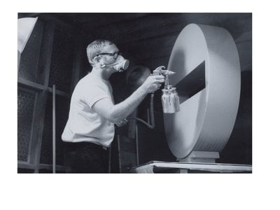 Photograph of Tony DeLap spray painting sculpture in Costa Mesa studio (detail), 1970 March / unidentified photographer. Tony DeLap papers, circa 1950-2015. Archives of American Art, Smithsonian Institution.