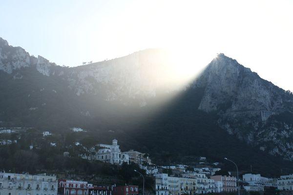 The sun shines through Monte Solaro on the island of Capri. thumbnail