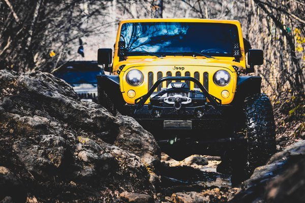 Yellow Jeep Wrangler in the Woods thumbnail