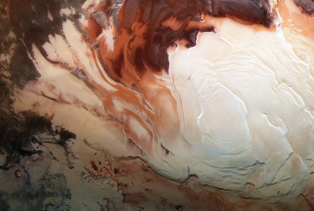 An image of Mars's South Pole. The photo shows a white icy cap surrounded by swirls of various shades of red.