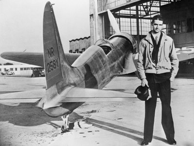 Howard Hughes stands with his first plane, the H-1.