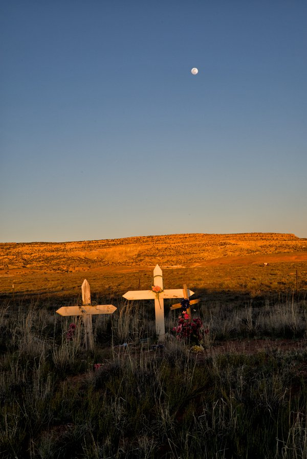 The moon rises over a roadside memorial. thumbnail