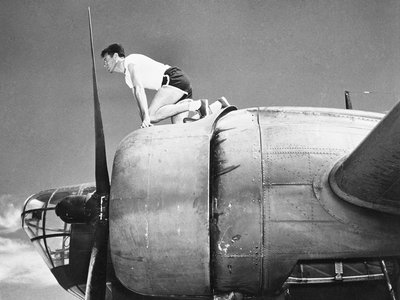 Olympian and airman Louis Zamperini crouches in his starting position on a B-18 bomber.