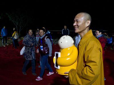 Xian'er, the robot monk, with its creator, Buddhist monk Master Xianfan.
