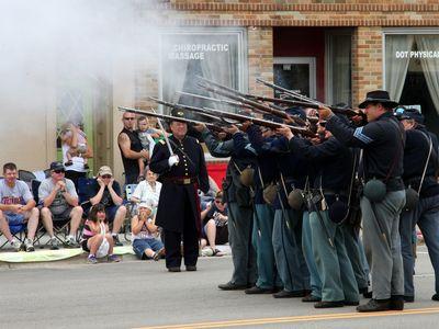 Civil War reenactors fire a salute in a public parade.
