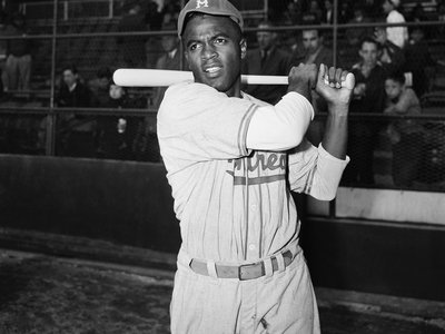 Jackie Robinson, is shown in post-swing position in front of the stands