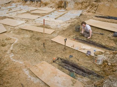 A researchers examines some of the graves unearthed in 2013