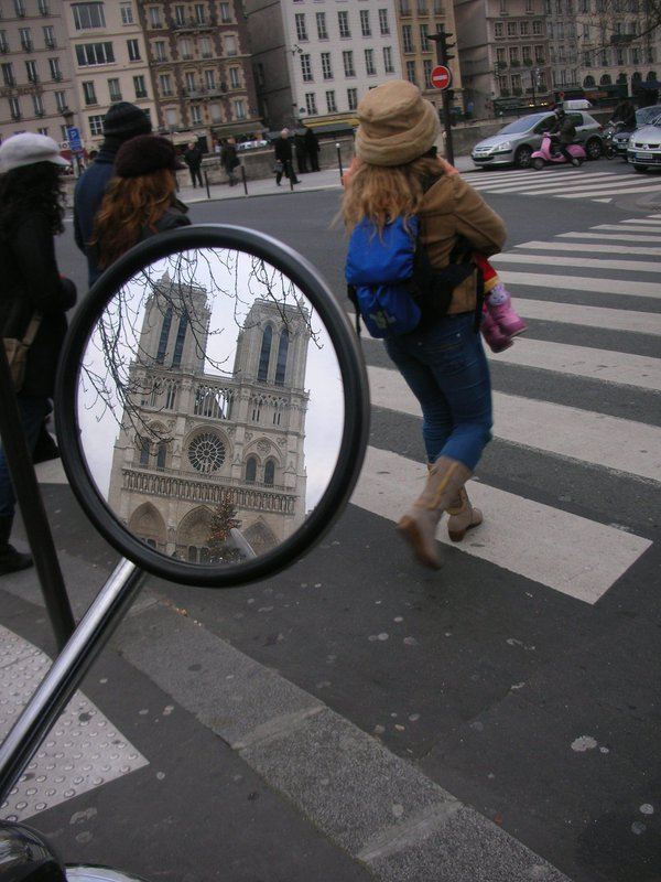 Notre Dame Cathedral, as seen in a moped rear-view mirror, across a crosswalk thumbnail