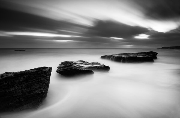 A long exposure after sunset captures the streaking clouds. The turbulent surf renders light in the scene, contrasting with the dark rocks. thumbnail