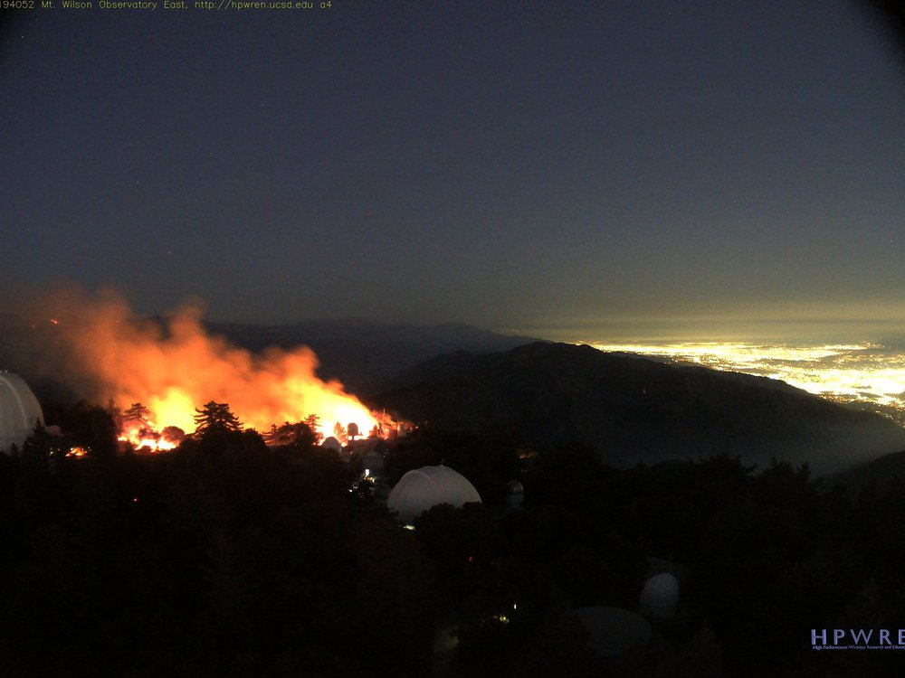 A panoramic shot of the soft glow of Pasadena and Los Angeles to the right, an expanse of dark nighttime hills, two white domed telescopes on the left with tall, bright orange and yellow flames bursting nearby, dramatic against the darkness