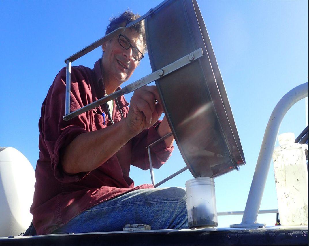 Man on boat taking samples