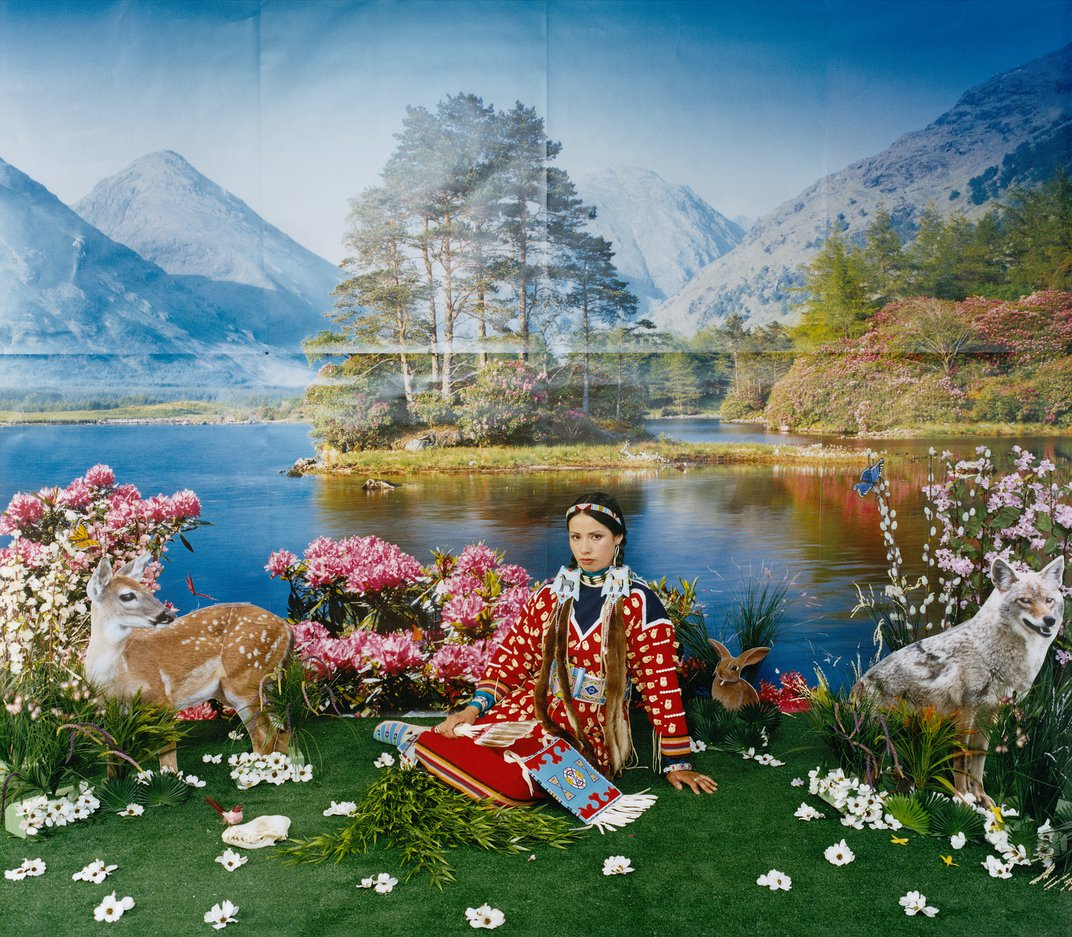 Native woman sitting on a grassy patch with a blow up deer next to her and a mountain landscape
