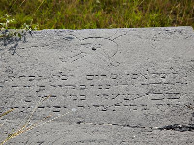 A grave marker in Kingston's Hunt's Bay Cemetery carved with a skull and crossbones and Hebrew lettering